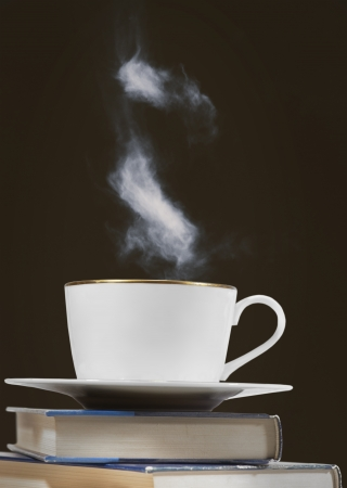 steaming coffee: Cup of coffee or other hot drink on pile of books with brown background Stock Photo