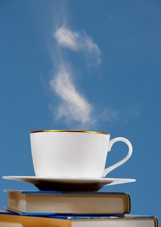 steaming: Cup of coffee on pile of books with blue background  Background is actually sky with fluffy white cloud Stock Photo
