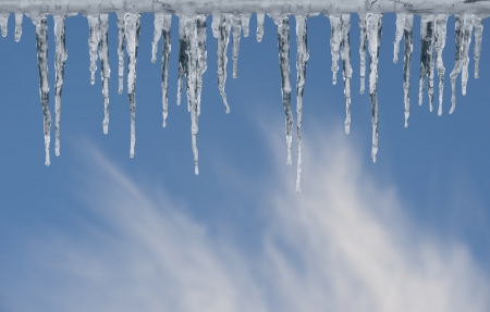 Row of icicles on bright blue winter sky