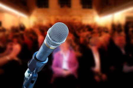 Close up of microphone in concert hall, with audience in background Foto de archivo