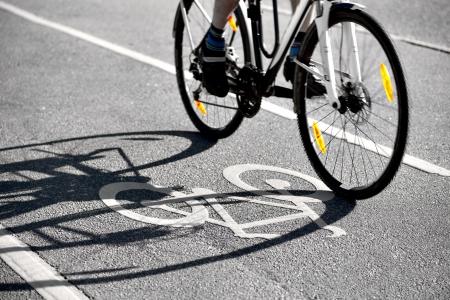 自転車自転車自転車レーンのシンボルに影を落として