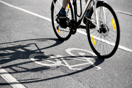 Cyclist casting a shadow on bicycle symbol on cycling lane