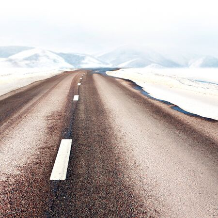 Asphalt road disappearing into winter mountain landscape Stock Photo