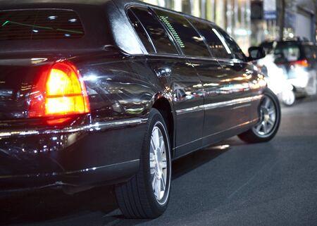 Niski kąt czarnej limuzyny w mieście w nocy