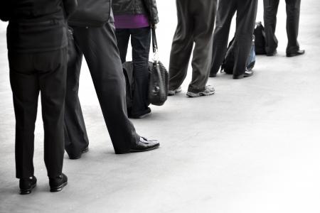 file d attente: Les gens en v�tements sombres avec des sacs en attente dans la file d'attente