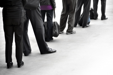 People in dark clothes with bags waiting in queue Stock Photo