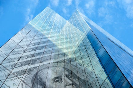 Office building with hundred dollar bills on blue sky with fluffy clouds