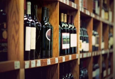 wood shelf: Botellas de vino en estante de madera en la tienda de vinos