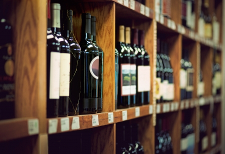 Wine bottles on wooden shelf in wine store