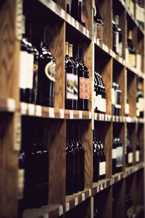 beverage display: Wine bottles on wooden shelf in wine store  Vintage look