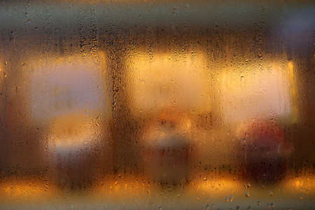 Background with glass window with rain or steam, and display of cup cakes in warm light inside  photo