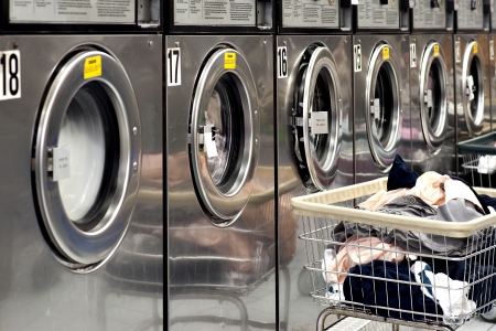 Row of industrial washing machines in a public laundromat, with laundry in a basket