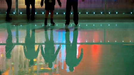 skating fun: People in ice skating rink with mulii colored lights