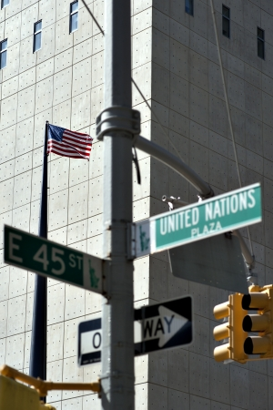 united nations: American flag and street sign outside United Nations building in New York  Focus on flag