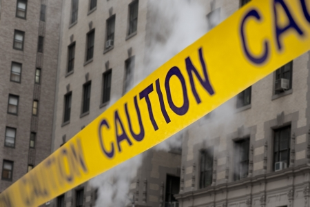 fire safety: Caution yellow tape in front of building with smoke Stock Photo