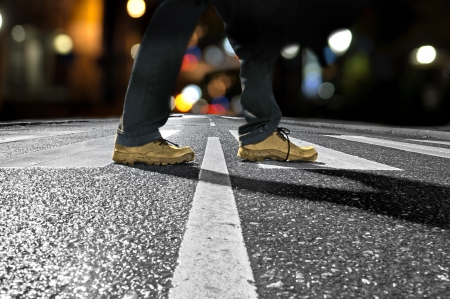 people walking street: Feet of man crossing street late at night Stock Photo
