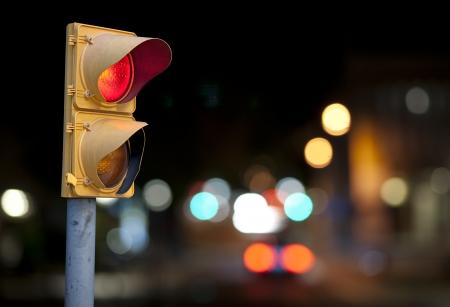 バック グラウンドで街の灯で夜に赤信号