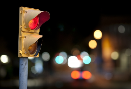 Red traffic light at night with city lights in background Banque d'images