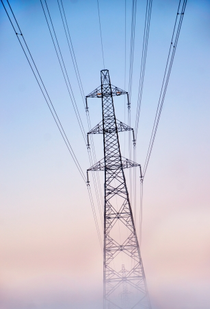 electricity pylon: Electricity pylon in heavy fog at sunset in winter