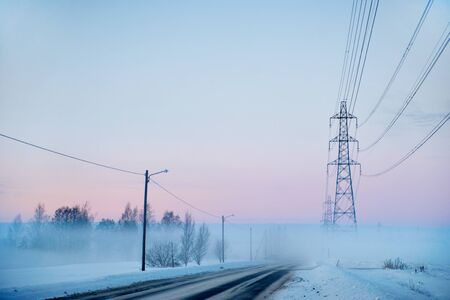 Country road with electricity pylons on foggy winter evening photo