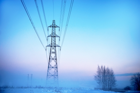 Electricity pylon in heavy fog at sunset in winter photo