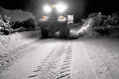 Heavy vehicle in blurred motion clearing snow on suburban road at night photo