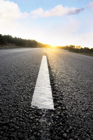 dividing: Close up of dividing line on asphalt road at sunset
