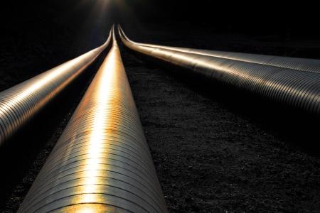 Pipelines reflétant la lumière du soir, disparaissant dans l'obscurité
