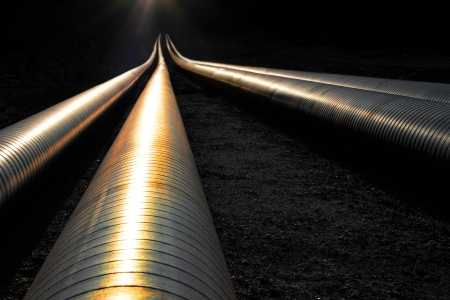 petroleum: Pipelines reflecting the evening light, disappearing into darkness Stock Photo