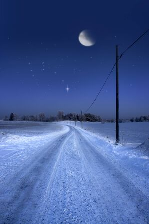 ursa minor: Rural dirt road in winter evening with moon and stars in sky
