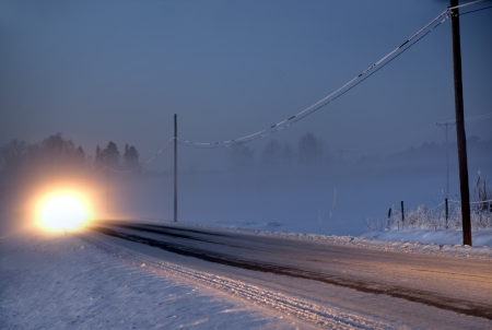 Headlights of car on rural road in winter evening with heavy fog photo