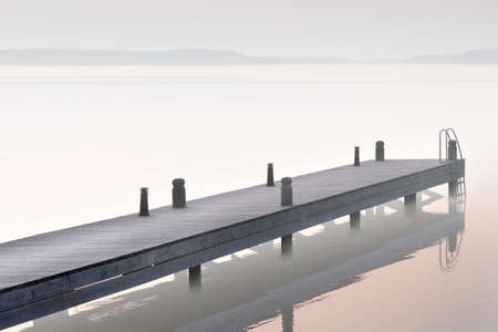 sparse: Sparse image of jetty in foggy lake Stock Photo