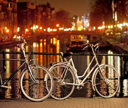 アムステルダムで橋の上に夜に駐車バイク 写真素材