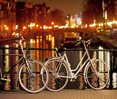 Bikes parked on bridge in Amsterdam at night