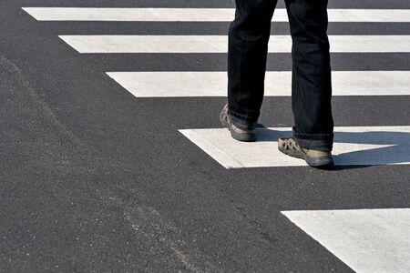 crossing legs: Legs of man in black jeans and sneakers crossing street