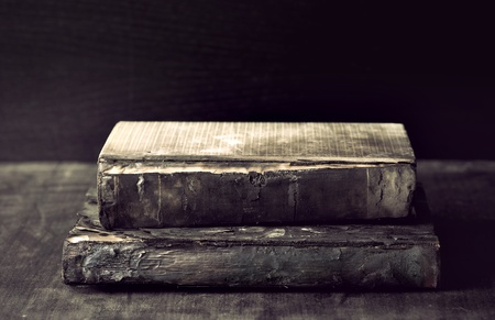 bad condition: Two ancient dirty  books in bad condition on dark wood