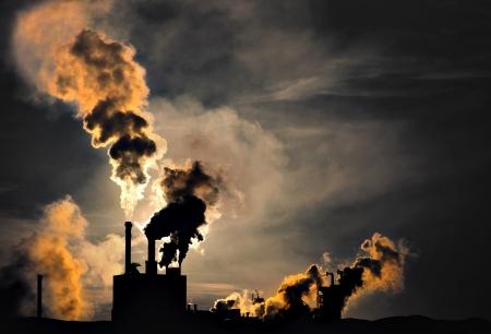 dioxido de carbono: Silueta de la fábrica con las chimeneas y el humo pesado Editorial