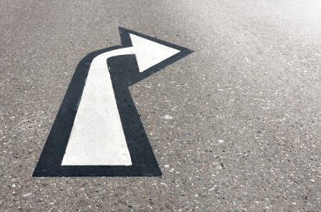 bright future: white arrow on asphalt pointing to bright future
