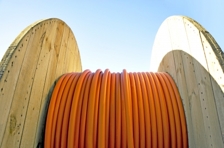 Wooden cable drum with orange cable on blue sky