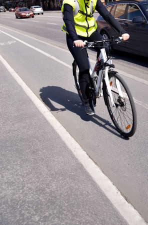 busy street: cyclist in bicycle lane by street with busy traffic
