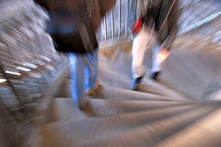 people in blurred motion walking in spiral staircase photo