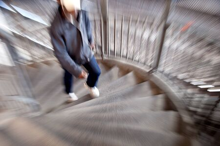 young man in blurred motion walking up spiral staircase photo