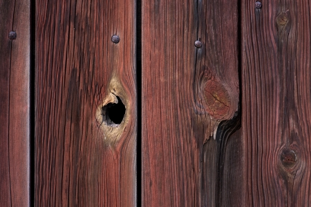 Red wooden grunge wall with peephole Stock Photo
