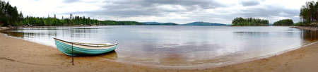 panoramic view of beach of scandinavian lake, with moored wooden rowboat photo
