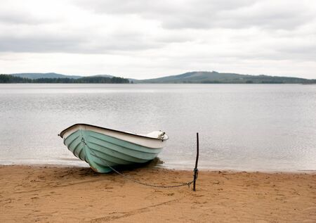 scandinavian landscape: Close up of boat moored on sandy beach of scandinavian lake Stock Photo
