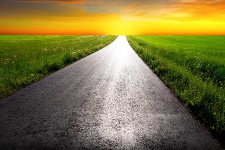bright future: country road leading into orange sunrise Stock Photo