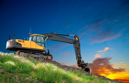 digger: Digger on hill with grass and flowers at sunset