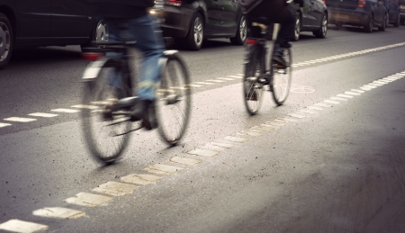 bicycle lane: Cyclists in blurred motion in busy street on gloomy rainy day Stock Photo