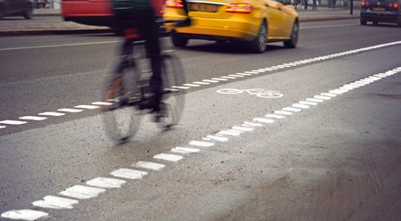bicycle lane: Cyclist in blurred motion in busy street on gloomy rainy day