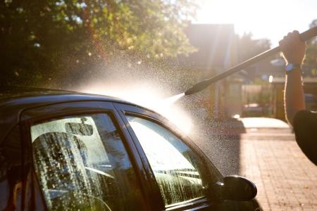 Mann Waschen Auto in der Sonne mit Hochdruckreiniger